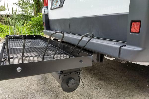 Sewer/grey tank drain hose storage tube mounted on bike/cargo carrier.